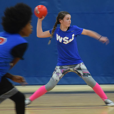 Girl throwing a dodgeball participating in our teen dodgeball league