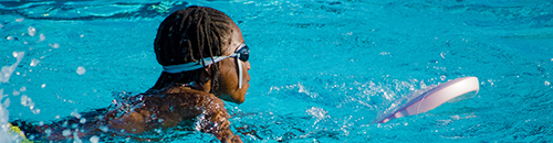 A girl swimming in a pool holding a small kick board and wearing swimming goggles.